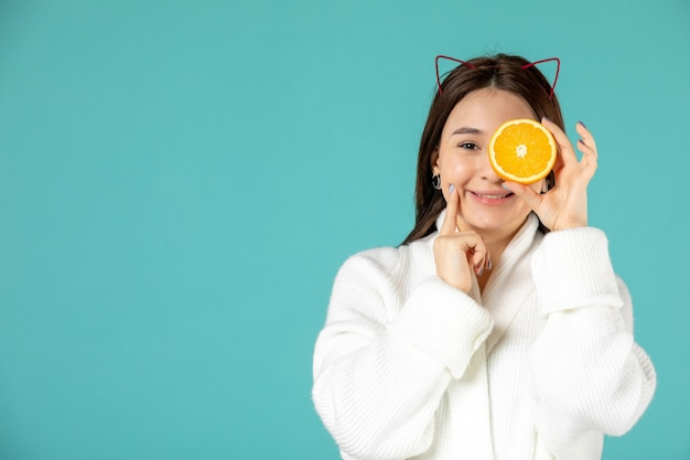 Front view young female in bathrobe holding orange slice on blue background