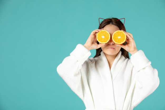 Front view young female in bathrobe holding orange slices on blue background