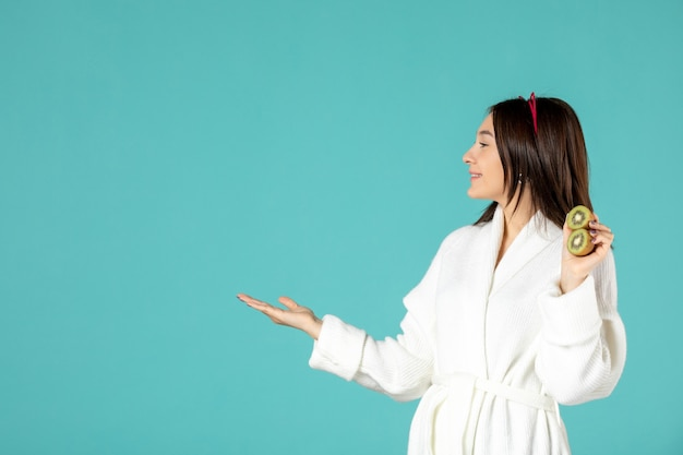 Front view young female in bathrobe holding sliced kiwis on blue background