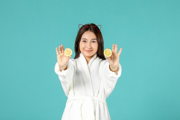 Vista frontale giovane donna in accappatoio con limoni a fette su sfondo blu
