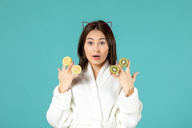 Vista frontale giovane donna in accappatoio che tiene fette di limone e kiwi su sfondo blu