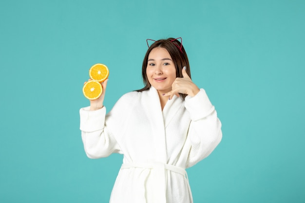 Front view young female in bathrobe holding sliced orange on blue background