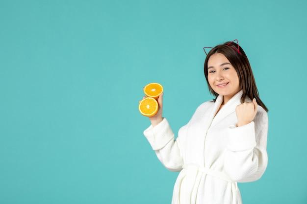 Vista frontale, giovane donna, in, accappatoio, presa a terra, arancia affettata, su, blu, background