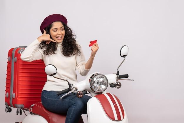 Vista frontale giovane donna in bicicletta con carta di credito rossa su sfondo bianco città colore veicolo stradale moto velocità vacanza soldi