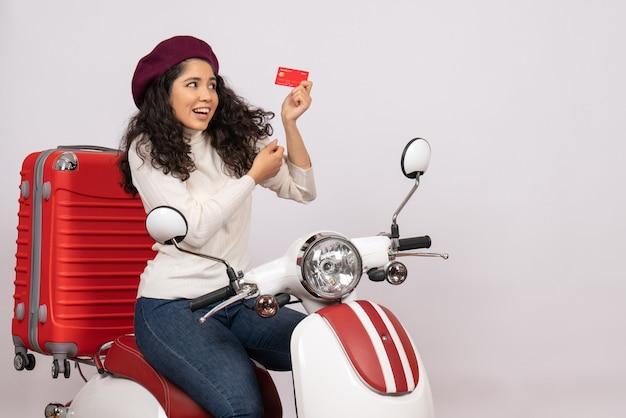 Vista frontale giovane donna in bicicletta in possesso di carta di credito rossa su sfondo bianco città veicolo stradale moto velocità vacanza denaro colore