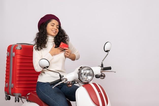 Vista frontale giovane donna in bicicletta in possesso di carta di credito rossa su sfondo bianco città veicolo stradale moto velocità vacanza soldi
