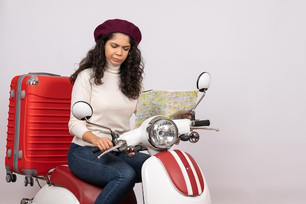 Front view young female on bike observing map on a white background city color road vacation vehicle motorcycle ride speed