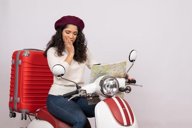 Vista frontale giovane donna in bicicletta osservando la mappa su sfondo bianco colore velocità su strada veicolo in motocicletta
