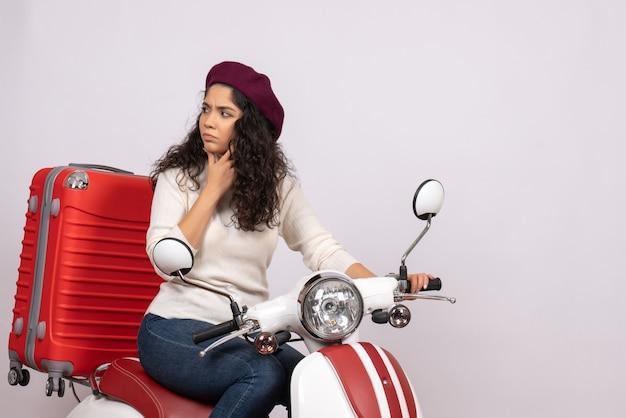 Vista frontale giovane donna in bicicletta con la sua borsa su sfondo bianco colore corsa su strada vacanza veicolo