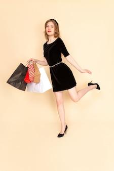 Una giovane femmina di vista frontale in vestito nero con la cinghia della catena che tiene i pacchetti di acquisto sul beige