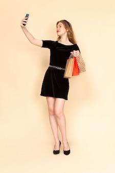 Una giovane donna di vista frontale in abito nero con cintura a catena tenendo i pacchetti della spesa e prendendo un selfie sul beige