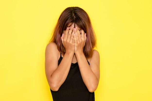 Vista frontale della giovane donna in camicia nera e jeans grigi che copre il viso sulla parete gialla