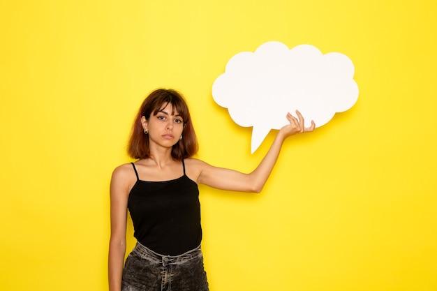 Vista frontale della giovane donna in camicia nera e jeans grigi con cartello bianco sulla parete gialla