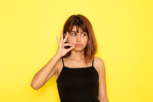 Vista frontale di giovane donna in camicia nera e jeans grigi che posano appena sulla parete gialla