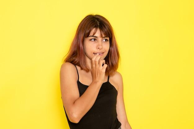 Vista frontale della giovane donna in camicia nera e jeans grigi in posa sulla parete gialla