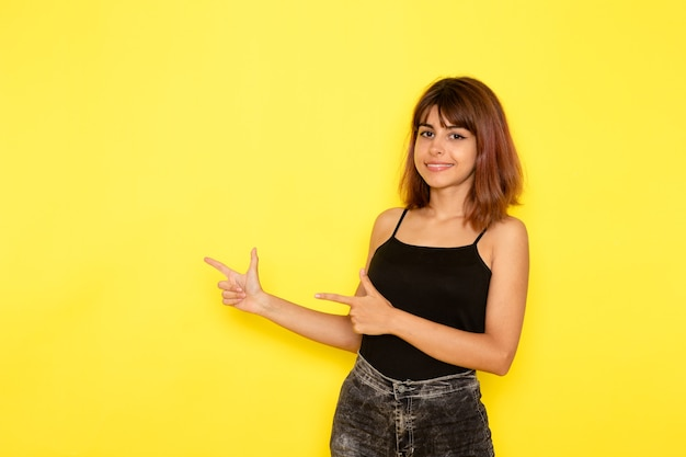 Vista frontale di giovane donna in camicia nera e jeans grigi sorridente e in posa sulla parete gialla