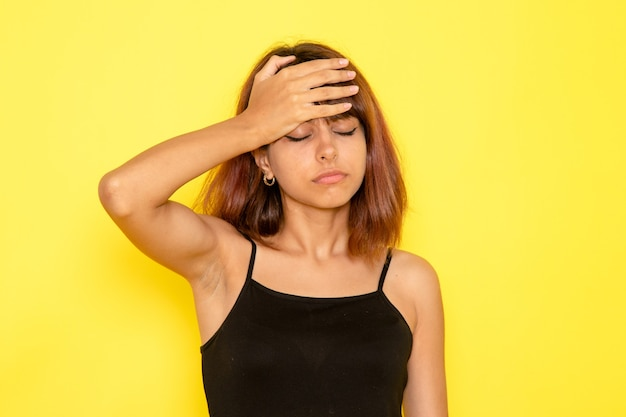 Vista frontale della giovane donna in camicia nera e jeans grigi che soffrono di mal di testa sulla parete gialla