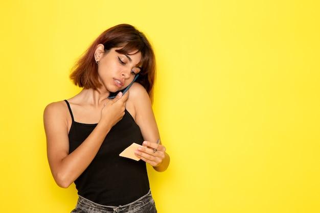 Vista frontale della giovane donna in camicia nera e jeans grigi, parlando al telefono sulla parete gialla