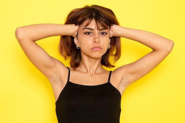 Vista frontale della giovane donna in camicia nera e jeans grigi che tocca i suoi capelli sulla parete gialla