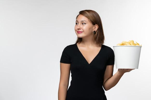 Giovane femmina di vista frontale in camicia nera che tiene le patatine fritte sulla superficie bianca chiara