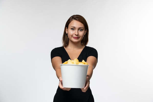 Front view young female in black shirt holding potato chips and watching movie on a white surface