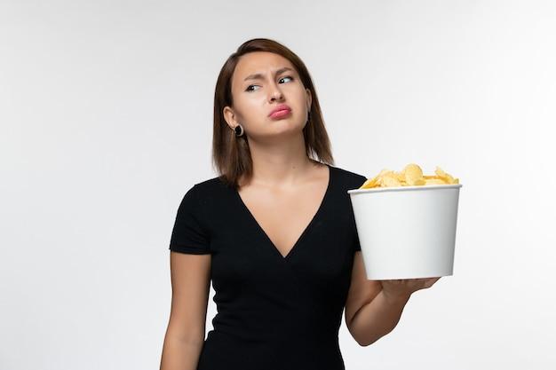 Giovane femmina di vista frontale in camicia nera che tiene patatine fritte sulla superficie bianca