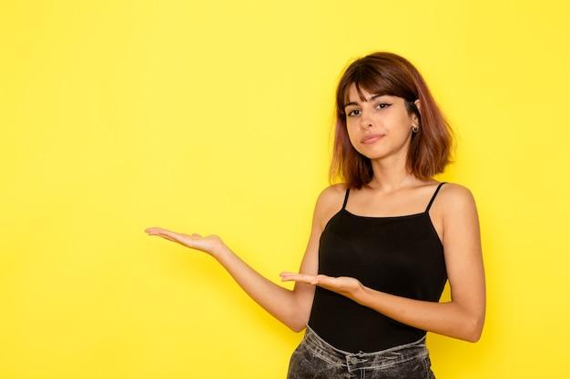 Vista frontale della giovane donna in camicia nera in posa sul muro giallo chiaro