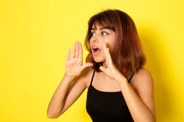Vista frontale della giovane donna in camicia nera che bisbiglia e chiama sul muro giallo chiaro