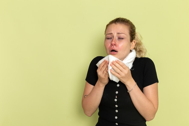 Front view young female in black shirt white towel around her throat feeling very sick and ill sneezing on green wall illness sickness female color health