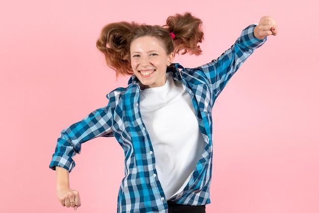 Vista frontale giovane donna in camicia a scacchi blu che salta sul muro rosa donna emozioni modello moda ragazze colore