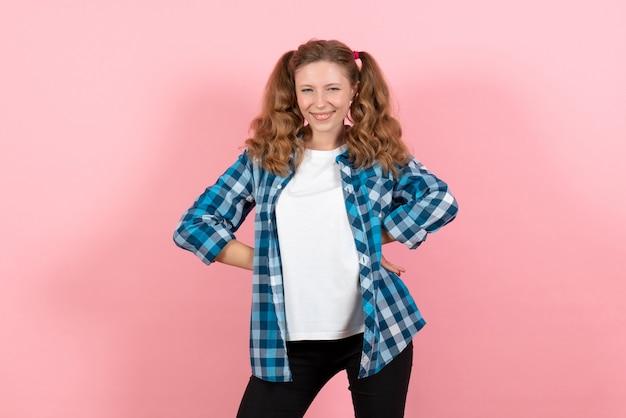 Vista frontale giovane femmina in camicia a scacchi blu in posa su sfondo rosa emozione ragazza modello moda bambino giovanile
