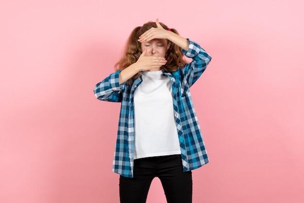 Vista frontale giovane femmina in camicia a scacchi blu in posa su sfondo rosa kid ragazza emozione giovanile moda modello