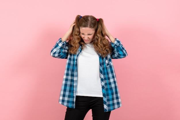 Vista frontale giovane femmina in camicia a scacchi blu in posa su sfondo rosa kid ragazza emozioni giovanili moda modello