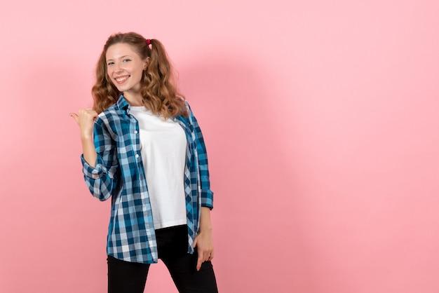 Vista frontale giovane femmina in camicia a scacchi blu in posa su sfondo rosa kid gioventù emozione modello moda donna colore