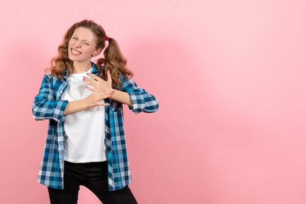 Front view young female in blue checkered shirt posing on pink background kid youth emotion model woman color