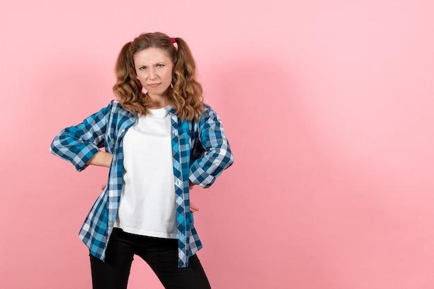 Vista frontale giovane femmina in camicia a scacchi blu in posa su sfondo rosa donna emozione ragazza moda modello di colore
