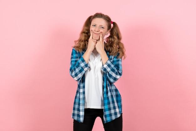 Vista frontale giovane femmina in camicia a scacchi blu in posa su sfondo rosa donna emozione ragazza moda colori modello