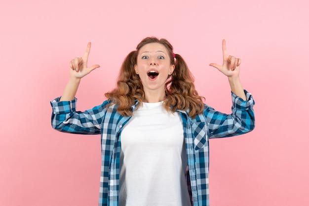 Giovane femmina di vista frontale in camicia a quadretti blu che posa sul colore rosa delle ragazze di modo del modello di emozione della donna del fondo