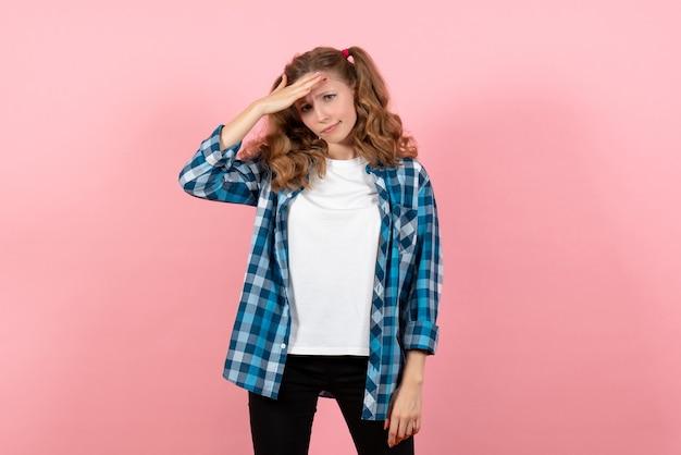 Vista frontale giovane femmina in camicia a scacchi blu in posa su sfondo rosa donna bambino modello giovanile colore emozione