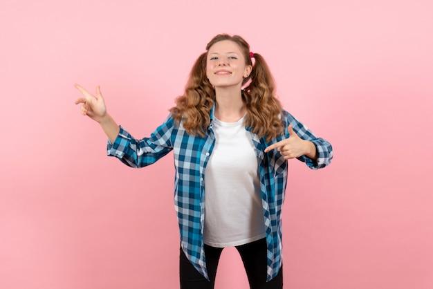 Vista frontale giovane femmina in camicia a scacchi blu in posa su uno sfondo rosa emozione giovanile ragazza ragazzino moda modello