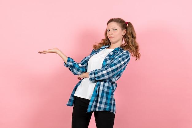 Giovane femmina di vista frontale in camicia a quadretti blu che posa sul capretto rosa della gioventù del modello di colore della ragazza di emozione dello scrittorio