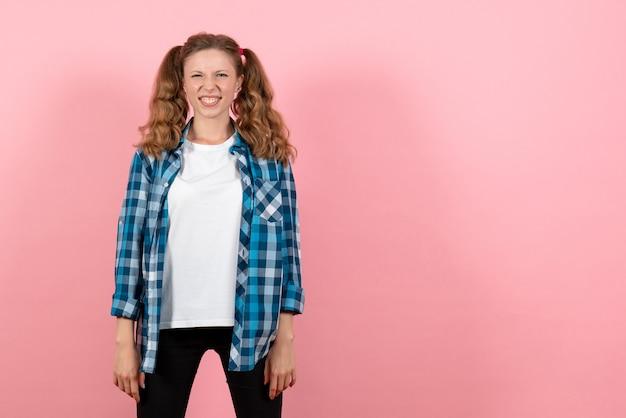 Giovane femmina di vista frontale in camicia a scacchi blu in posa sul modello di colore rosa donna emozione ragazza moda colore