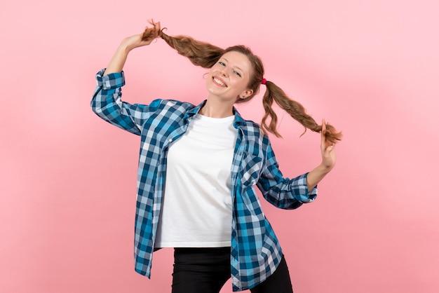 Vista frontale giovane donna in camicia a scacchi blu in posa e sorridente sul muro rosa donna emozioni modello moda ragazze colore