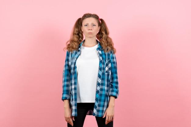 Vista frontale giovane femmina in camicia a scacchi blu in posa con espressione pazza su sfondo rosa donna emozioni ragazze colore modello moda