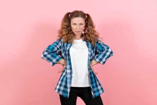 Vista frontale giovane femmina in camicia a scacchi blu in posa con espressione pazza su sfondo rosa donna emozioni modello moda ragazze colore