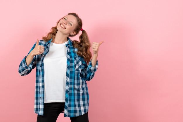 Vista frontale giovane femmina in camicia a scacchi blu in posa con un sorriso su sfondo rosa emozione ragazza modello moda gioventù kid