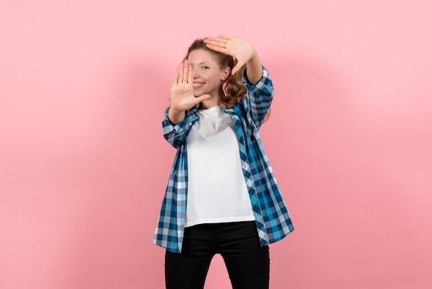 Giovane femmina vista frontale in camicia a scacchi blu in posa con il sorriso su sfondo rosa kid ragazza emozioni giovanili moda modello