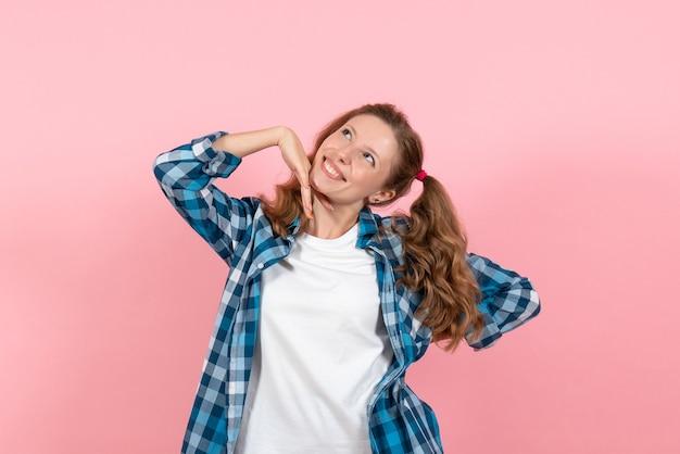 Giovane donna di vista frontale in camicia a scacchi blu in posa con il sorriso sullo sfondo rosa donna emozioni modello moda ragazze colore