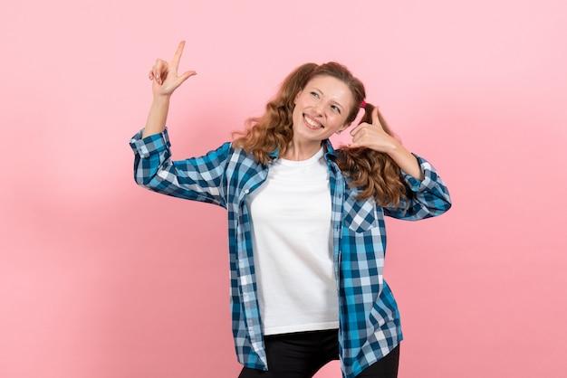 Vista frontale giovane femmina in camicia a scacchi blu con felice espressione sullo sfondo rosa donna emozioni modello moda ragazze colore