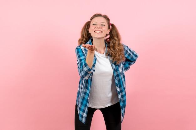 Vista frontale giovane femmina in camicia a scacchi blu con felice espressione su sfondo rosa emozione giovanile ragazza ragazzino moda modello